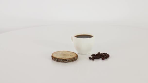Kaffeetasse mit Kaffeebohnen auf weißem Tischhintergrund