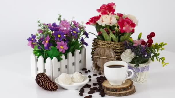 coffee cup with candies and flowers on wooden table background