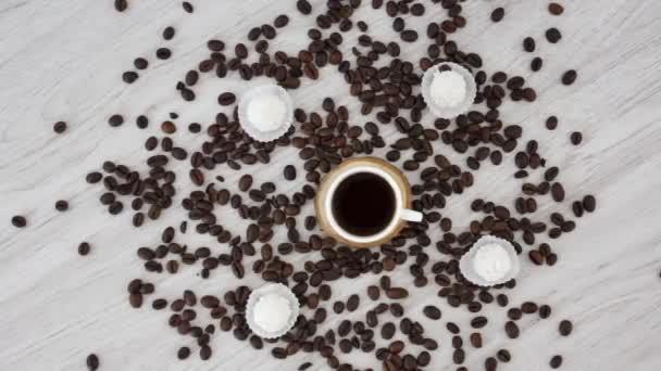 šálek černé kávy s bonbóny na dřevěném stole pozadí