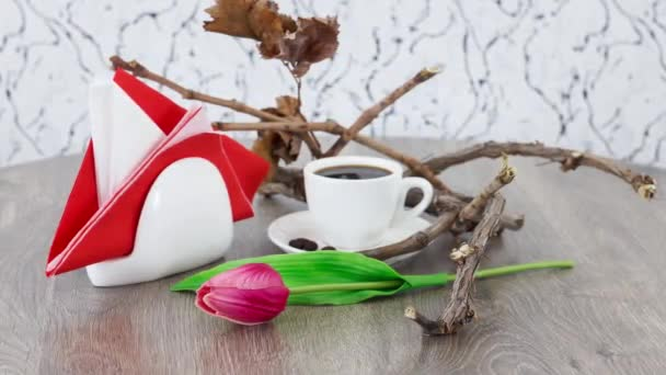cup of black coffee with tulip on wooden table background
