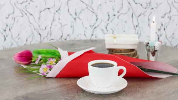 cup of black coffee with candle and flowers on wooden table background