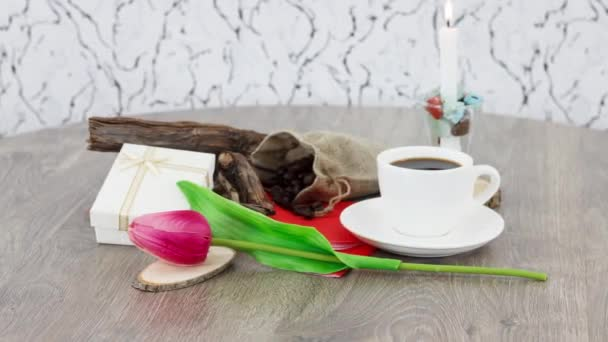 cup of black coffee with candle on wooden table background