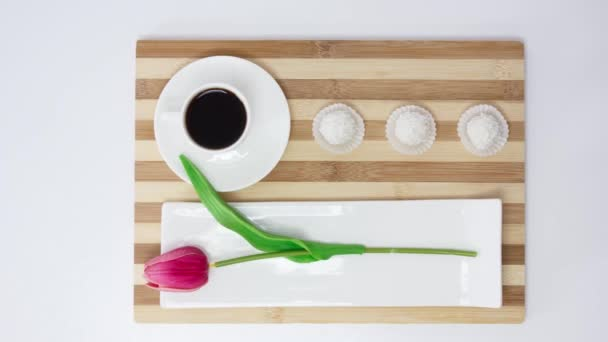 white mug with black coffee with sweets on table background