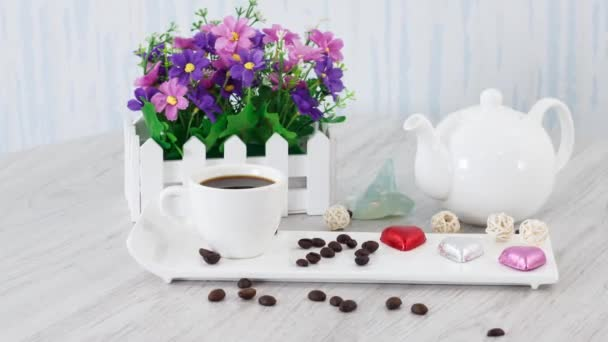coffee cup with candies and kettle on wooden table background