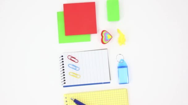 top view of colored office supplies and consumables on white rolling table background