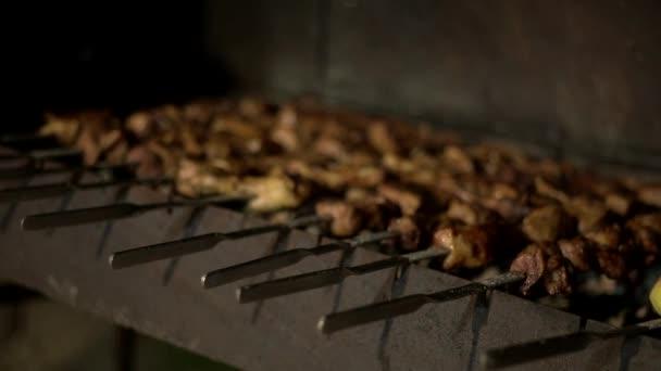 muž vaření grilované maso kuřecí špejle s křupavou kůrkou ve večerních hodinách