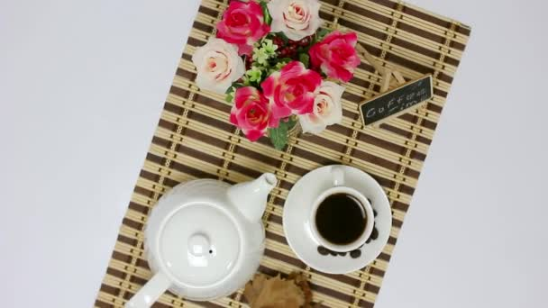 Coffee cup with flowers on wooden mat