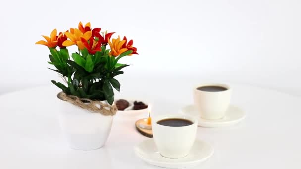 coffee cups with candies and candle on wooden table background
