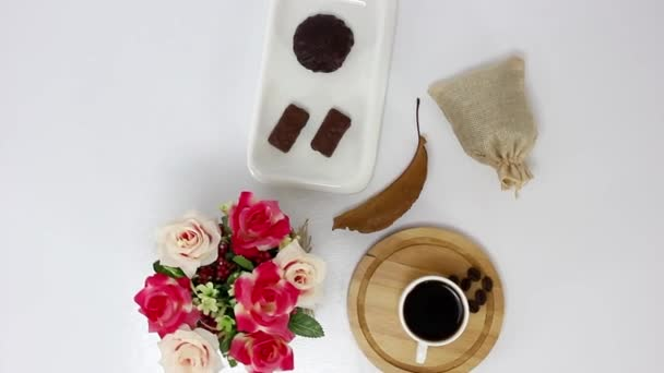 Cup of coffee with vase with flowers and cone on spinning wooden table background.