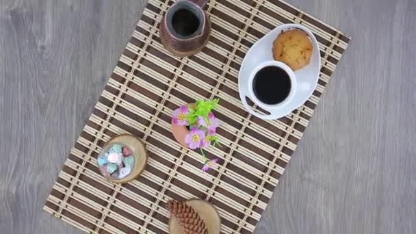bílý šálek kávy s chutnými sladkostmi na dřevěném stole pozadí