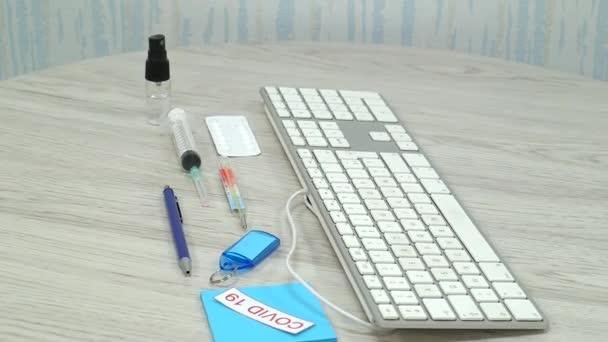 klávesnice s lékařskou vakcínou chránící před koronavirem na dřevěném podkladě stolu