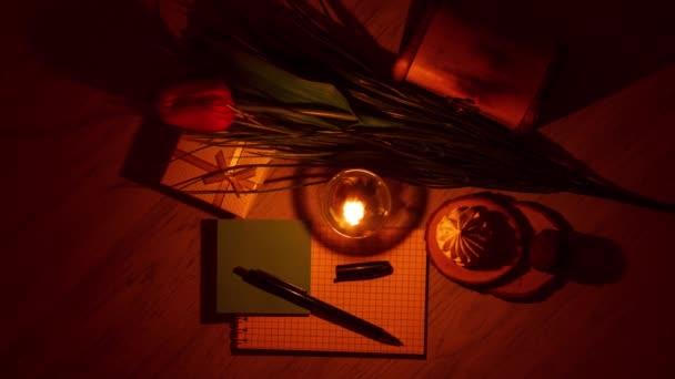 Hořící svíčky a kancelářské potřeby na abstraktním barevném pozadí. Barevný bokeh