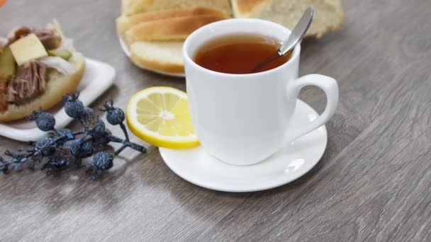 tasty morning breakfast with bread meat sandwich and tea cup on wooden table background