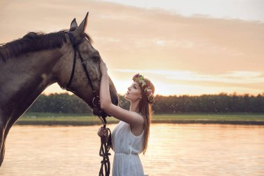 Pretty blond girl stroking a horse