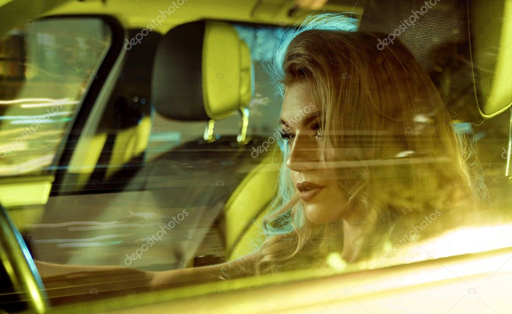 Attractive young woman sitting behind the wheel
