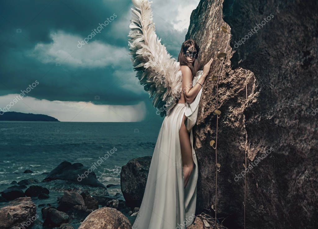 Beautiful young angel climbing on the clif