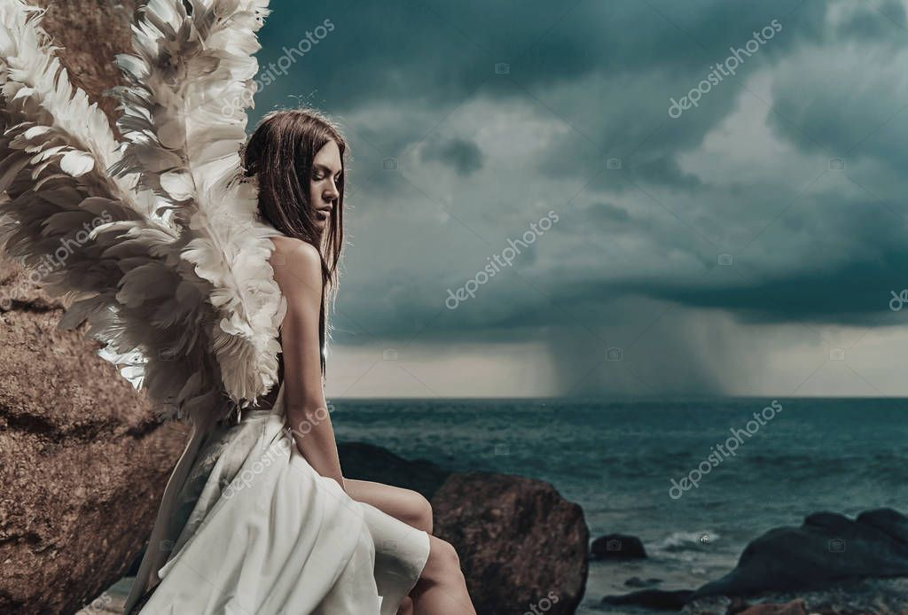 Sad angel looking at the occean
