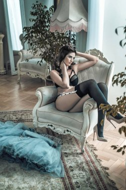 Sensual brunette model resting in the luxury apartment