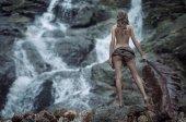 Nude lady watching a waterfall