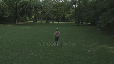 Fit, young woman stretching in the summer park