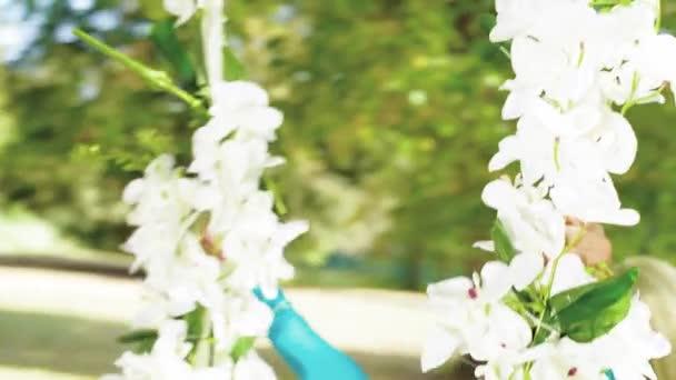 Atraktivní blondýnka na houpačce z květů