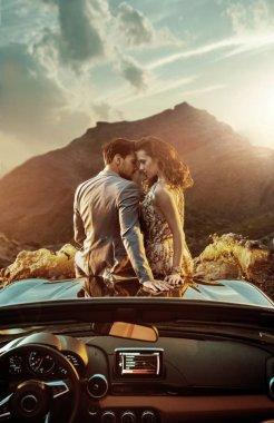Romantic couple sitting on the bonnet