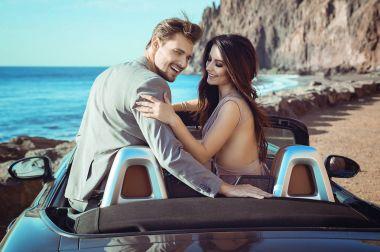 Smart couple riding a luxurious convertible