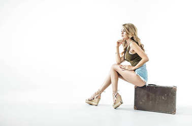 Pretty blonde sitting on the luggage, isolated