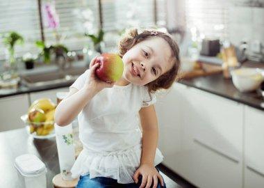 Cheerful kid holding an apple, kitchen shot