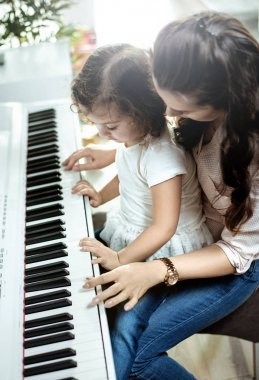 Young mom playing piano with her little daughter
