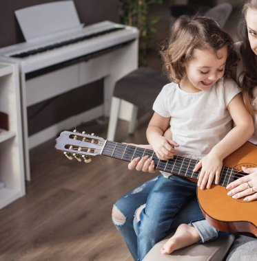 Mother and daughter playing a guitar