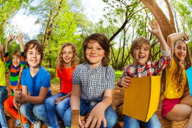 kids reading book in forest
