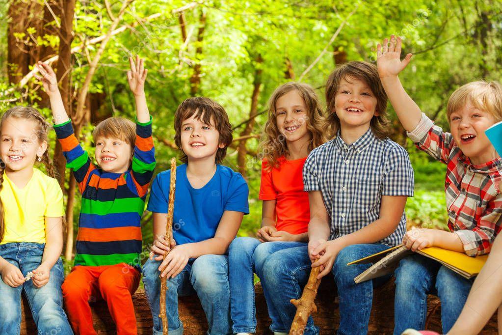 kids sitting on log outdoor