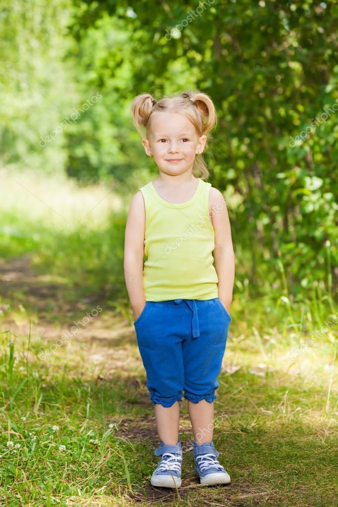 Cute little girl in green park