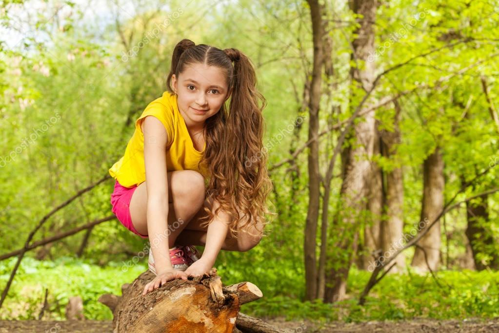 girl posing on log in forest