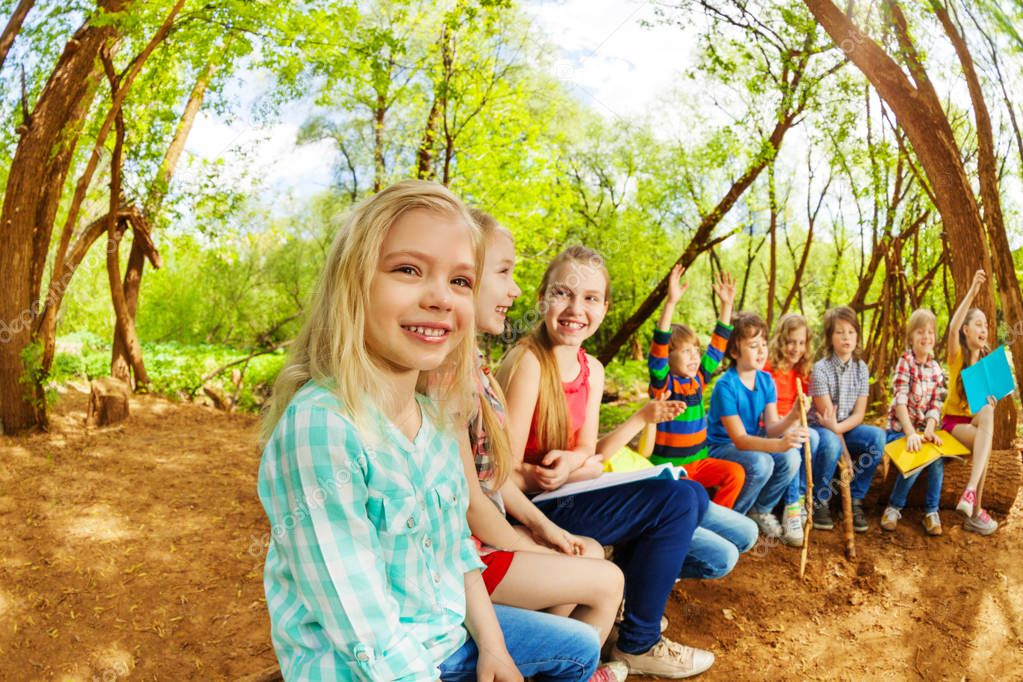 kids sitting on log
