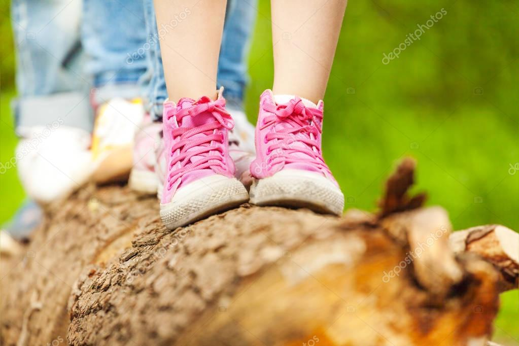 Children standing on log