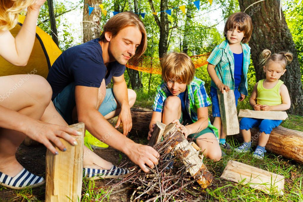 Father teaching kids to make campfire