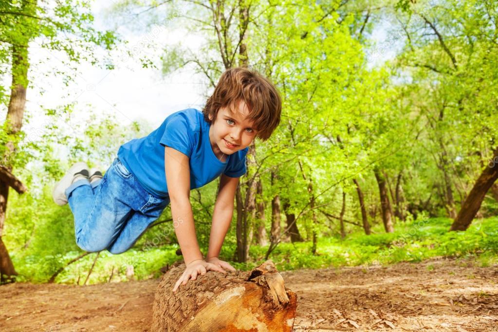 boy jumping over log