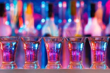 Five burning drinks in shot glasses