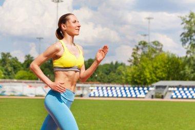 young woman running at stadium tracks