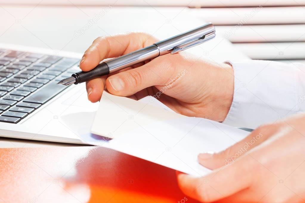 woman using laptop and making notes