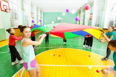 boys and girls playing parachute games