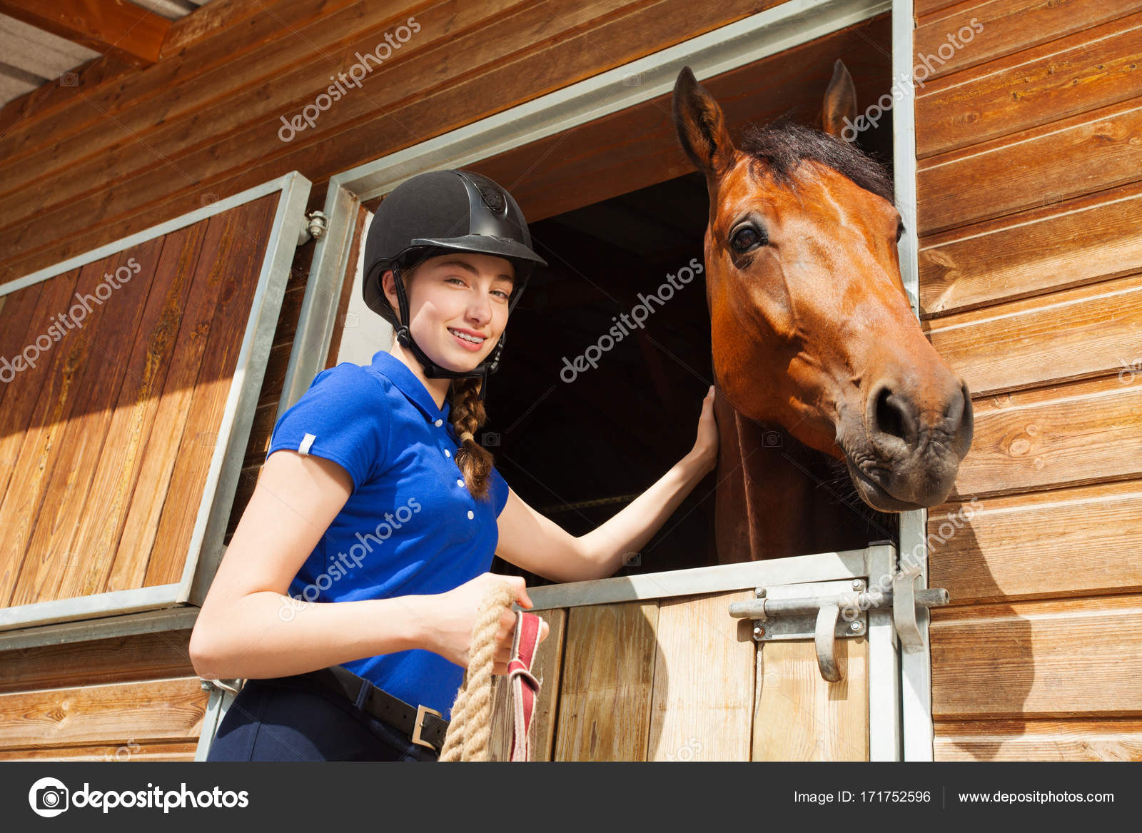 reiterin streichelt pferd im reitstall — stockfoto