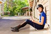 Fotografie Reiterin sitzt mit Peitsche vor einem Kastenstand