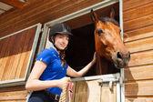 Reiterin streichelt Pferd im Reitstall