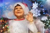 Megható a hideg fagyos ablak és mosoly boldog kisfiú Santa Claus kalap alatt a karácsonyfa közelében éjszakai
