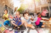 Group of kids with hands full of chalk showing palms and smiling drawing hopscotch