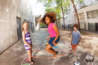 Kids jump over elastic rope smiling and happy with curly African girl in the air
