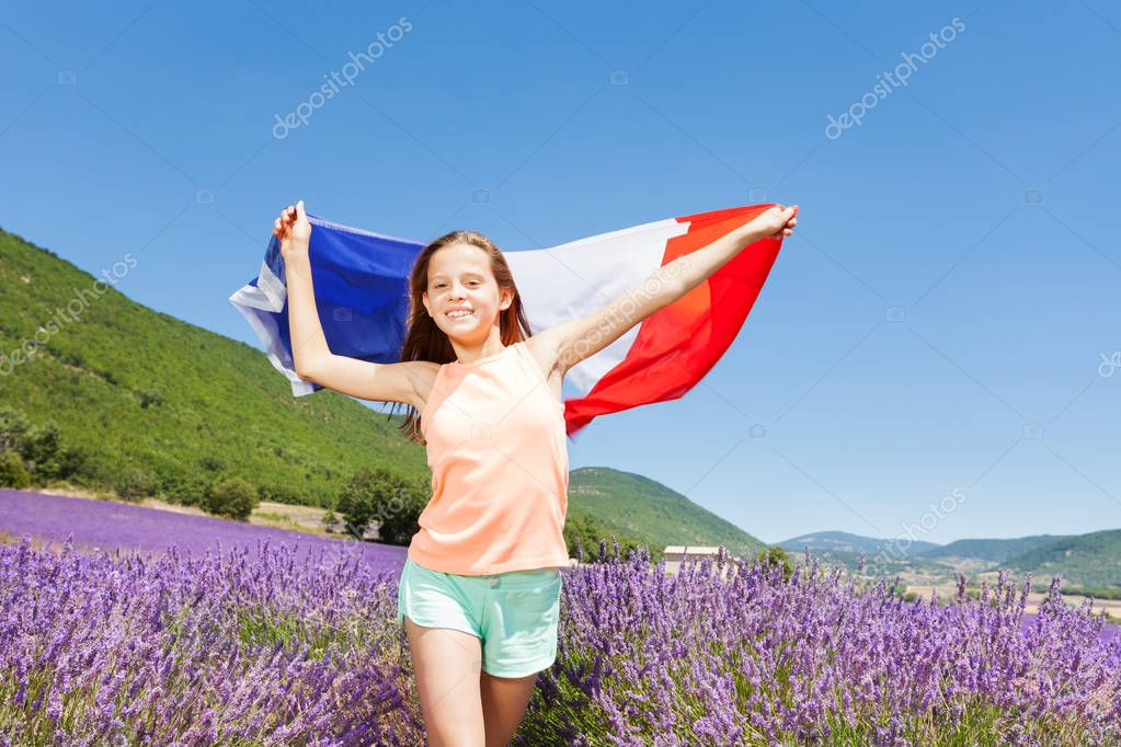 Portrait of smiling preteen girl waving French flag while running in lavender field in summer